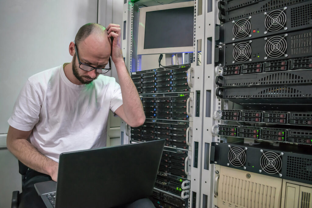 Picture of a man using a laptop inside of a data center